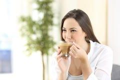 Mujer que bebe un café delicioso con leche Imagen de archivo
