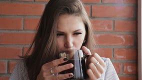 Mujer que bebe una bebida caliente en el apartamento del balcón metrajes