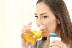 Mujer que bebe una medicina Imagenes de archivo