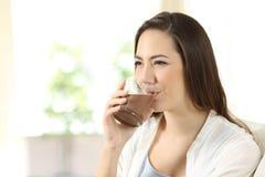Mujer que bebe una sacudida del cacao foto de archivo