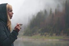Mujer que bebe una taza de café en el ajuste al aire libre Imagen de archivo