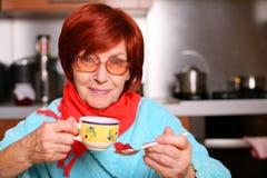 Mujer que bebe una taza de té con el atasco de frambuesa Fotografía de archivo libre de regalías