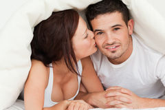 Mujer que besa al hombre en la mejilla Fotos de archivo