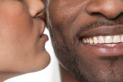 Mujer que besa al hombre negro en mejilla imagenes de archivo