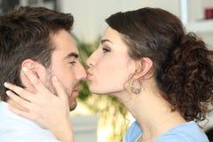 Mujer que besa a su novio Imagen de archivo libre de regalías