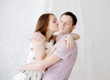 Mujer que besa a su novio en mejilla Fotos de archivo