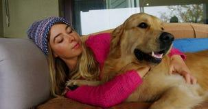 Mujer que besa su perro en el sofá en casa 4k almacen de video