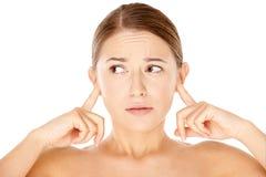 Mujer que bloquea sus oídos con sus fingeres Imagen de archivo libre de regalías
