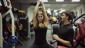 Mujer que bombea para arriba el tríceps con una pesa de gimnasia bajo supervisión de un instructor personal almacen de metraje de vídeo