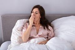 Mujer que bosteza en cama foto de archivo libre de regalías