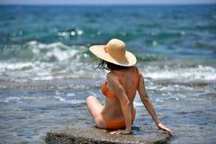 Mujer que broncea del bikini atractivo que se relaja en la playa con un sombrero Imagen de archivo