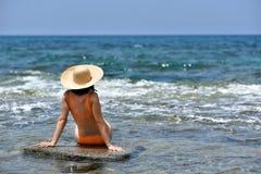Mujer que broncea del bikini atractivo que se relaja en la playa con un sombrero Foto de archivo