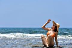 Mujer que broncea del bikini atractivo que se relaja en la playa con un sombrero Imagen de archivo libre de regalías