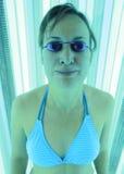 Mujer que broncea en solarium Imágenes de archivo libres de regalías