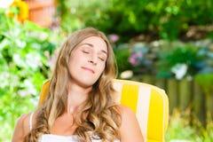 Mujer que broncea en su jardín en sillón Imagenes de archivo