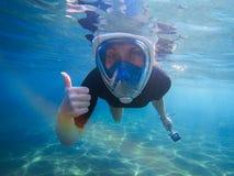 Mujer que bucea con el pulgar para arriba y la cámara de la acción Foto submarina del engranaje que bucea Fotografía de archivo