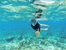 Mujer que bucea en agua de mar clara El tubo respirador muestra el pulgar en mascarilla completa Fotos de archivo