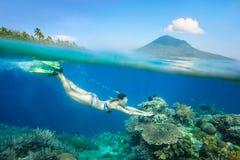 Mujer que bucea sobre el arrecife de coral hermoso foto de archivo