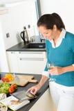 Mujer que busca el libro de las verduras de la cocina de la tablilla de la receta Fotos de archivo libres de regalías