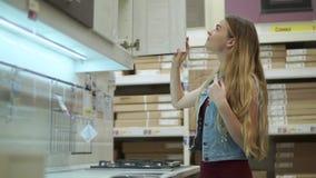 Mujer que busca el nuevo sistema de la cocina almacen de metraje de vídeo