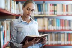 Mujer que busca los libros en la biblioteca Fotografía de archivo libre de regalías