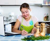 Mujer que busca nueva receta Foto de archivo libre de regalías