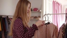 Mujer que busca un nuevo vestido, comprobando el precio en venta en boutique de la ropa Muchacha de la moda sorprendida por un co metrajes