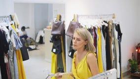 Mujer que cabe el vestido amarillo en el boutique Muchacha de moda y elegante que permanece delante del espejo Jóvenes y