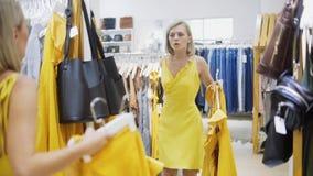 Mujer que cabe el vestido amarillo en el boutique Muchacha de moda y elegante que permanece delante del espejo Jóvenes y almacen de metraje de vídeo