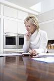 Mujer que calcula letras interiores con la calculadora en cocina Fotos de archivo
