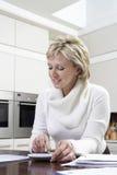 Mujer que calcula letras interiores con la calculadora en cocina Foto de archivo