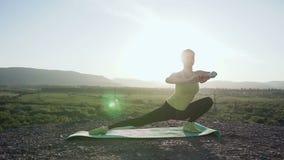 Mujer que calienta antes de entrenamiento de la aptitud en la salida del sol por la mañana Mujer que estira al aire libre en mont almacen de metraje de vídeo
