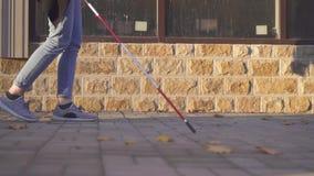 Mujer que camina abajo de la calle con un bastón para el MES con deficiencias visuales, lento almacen de video