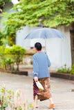 Mujer que camina abajo de la calle debajo de un paraguas en Louangphabang, Laos vertical Imagenes de archivo