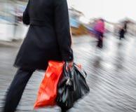 Mujer que camina abajo de la calle en la lluvia con un paquete rojo Imagen de archivo libre de regalías