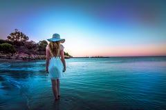 Mujer que camina abajo de la playa en la puesta del sol Imagenes de archivo