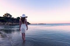 Mujer que camina abajo de la playa en la puesta del sol Fotos de archivo libres de regalías