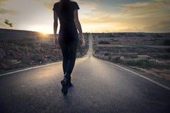 Mujer que camina abajo de una calle Fotos de archivo libres de regalías