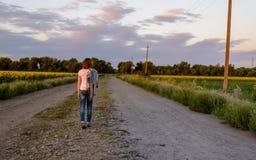 Mujer que camina abajo de una carretera nacional Imagen de archivo