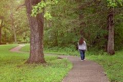 Mujer que camina abajo de una trayectoria en el bosque Imagenes de archivo