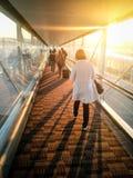 Mujer que camina abajo del finger del aeropuerto para conseguir al aeroplano con la luz del sol que brilla a través de las ventan Imagenes de archivo