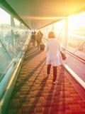 Mujer que camina abajo del finger del aeropuerto para conseguir al aeroplano con la luz del sol que brilla a través de las ventan Fotos de archivo