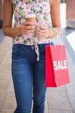 Mujer que camina con café para ir y el panier Foto de archivo libre de regalías