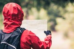 Mujer que camina con el mapa en bosque del otoño imágenes de archivo libres de regalías
