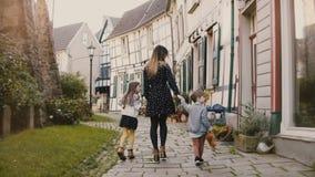Mujer que camina con el muchacho y la muchacha, llevando a cabo las manos Madre, dos niños Casas de entramado de madera Hattingen almacen de video