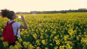Mujer que camina con la mochila roja y la botella de consumición de agua en el campo de las flores del amarillo de la rabina metrajes