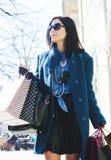 Mujer que camina con los bolsos después de buen hacer compras Foto de archivo