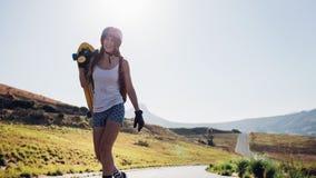 Mujer que camina con un longboard en el camino del campo Fotografía de archivo