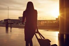 Mujer que camina con una carretilla en la puesta del sol Imagen de archivo libre de regalías
