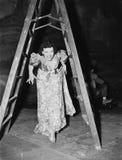 Mujer que camina debajo de una escalera de paso con sus fingeres cruzados (todas las personas representadas no son vivas más larg Imagenes de archivo